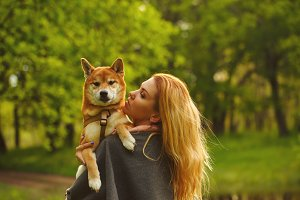 Girl and dog Shiba Inu hug.