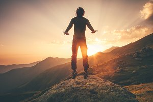 Man jumping in sunset mountains