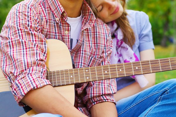 Teenage couple with guitar in park