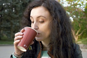 Brunette long hair girl portrait outdoors with tea