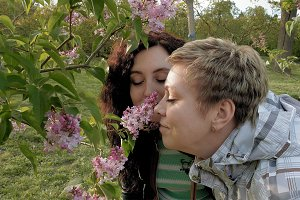 Two girls sniffing lilac flowers in the green park