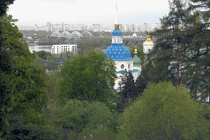 White blue and gold orthodox church in trees