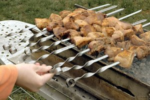 Barbeque skewers with meat cooking on brazier