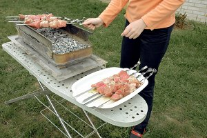 Girl puts barbecue skewers with meat on brazier