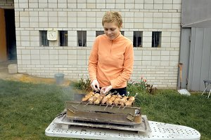 Girl cooks barbeque skewers with meat on brazier