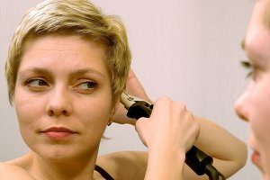 Short hair woman curls her hair with curling iron