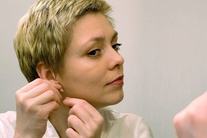 Pretty blond woman wears earrings and smartens up