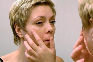 Woman applies makeup concealer foundation cream
