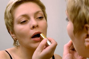 Pretty blond woman applying red lipstick makeup