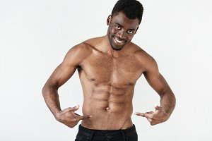 Portrait of young African American man with perfect muscular body. Dark skinned athlete male model in black jeans pointing at his nude chest looking with happy and confident expression at the camera.
