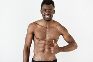Isolated portrait of healthy muscular dark skinned man with beautiful athlete body posing shirtless against white studio wall background. Handsome young African American male showing thumbs-up