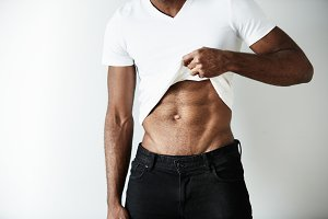 Cropped portrait of athletic African American male wearing black jeans and white blank T-shirt, showing his beautiful abdominals. Young man demonstrating muscles standing against white concrete wall