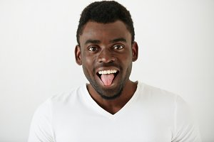 Close up portrait of African American student boy wearing white T-shirt making funny face, looking and showing tongue at the camera after classes at university. Attractive young male model having fun