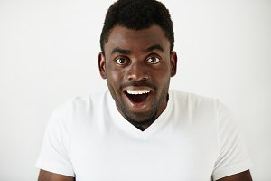 Close up of amazed young African American man in white blank T-shirt, having fun indoor, looking at the camera with excited expression, astonished with sale prices. Human face expressions and emotions