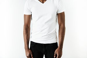 Cropped isolated portrait of athlete African American man wearing black jeans and white blank T-shirt with copy space for your text or promotional content. T-shirt design and advertising concept