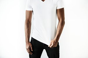 Cropped portrait of handsome young African American student wearing skinny black denim pants and white blank copy space T-shirt for your text or advertising content. Lifetsyle and people concept