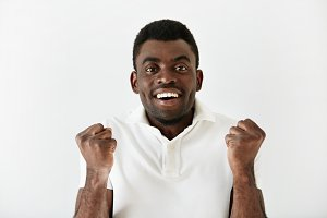 Headshot of happy successful African American student or businessman looking with winning expression, fists pumped, celebrating success against white wall background. Life perception, achievement