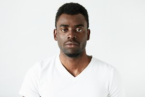 Isolated headshot of handsome African American adult man in white T-shirt, looking at the camera with serious and confident expression on his face posing against white studio wall background.