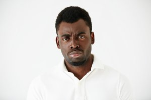 Close up shot of angry, grumpy or pissed off African American man with bad mood, looking and frowning at the camera, posing against white studio wall. Negative human face expressions and body language