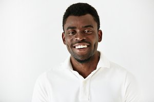 Close up portrait of handsome successful young dark skinned male entrepreneur in casual clothes, looking and smiling at the camera with confident and happy expression, achieveing business goals
