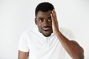 Headshot of handsome surprised African American young man looking at the camera, astonished with big sale prices against white background. Human face expression, emotion, feeling, reaction, attitude