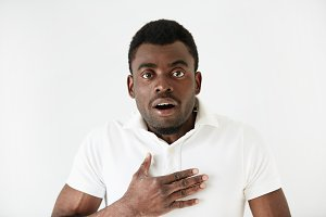 Isolated portrait of shocked young attractive African American male looking in full disbelief, hand on chest, surprised with some unexpected news. Positive human emotions and facial expressions