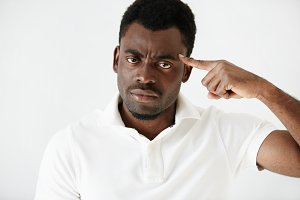 Close up portrait of angry young dark-skinned businessman wearing casual clothes, gesturing with index finger against his temple: are you crazy? Negative human emotions, facial expressions, feelings
