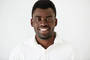Headshot portrait of handsome young African American man  with a beard wearing white blank T-shirt looking and smiling  at the camera against white studio wall background. People and lifestyle concept