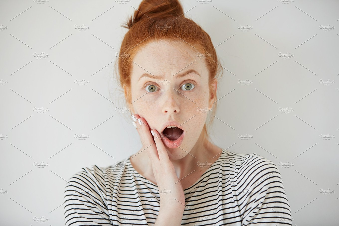 Young redhead woman with surprised facial expression ...