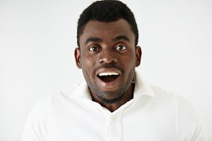 Closeup portrait of happy young handsome African American man looking excited and stunned with mouth wide open, isolated on white background. Positive human emotions, facial expressions and feelings