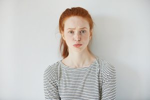 Closeup portrait of grumpy or annoyed young woman with red hair wearing striped top, looking at the camera with sad or unhappy expression on her face while having some problem at work. Body language