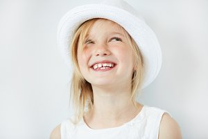 Close up portrait of adorable blonde little girl wearing white hat, laughing and having fun indoor. Cute 5-year old female smiling and showing her teeth. Isolated portrait of beautiful Caucasian child