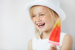 Selective focus. Portrait of little girl holding fruit ice cream, smiling and laughing against white studio wall background with copy space for your advertising content. Happy childhood concept