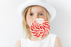 Close up shot of beautiful preschool child in stylish white clothes, enjoying sweet candy, posing against white copy space wall. Beautiful little girl with huge spiral lollipop. Selective focus