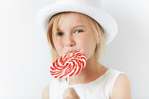 Close up image of happy little girl holding big spiral lollipop. Adorable blonde preschool child wearing fashionable white hat and dress, looking away, licking candy. Selective focus, film effect