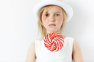 Close up portrait of beautiful preschool girl in white hat and dress loooking at the camera with sad and disappointed expression, holding huge spiral lollipop. Human face expressions and emotions