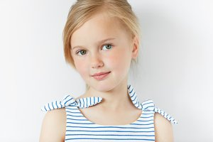 Isolated headshot of adorable preschool female model with fair hair posing in striped dress against white concrete wall background, looking and smiling at the camera. People and lifestyle concept