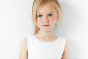 Close up shot of cute fashionable child with green eyes and blonde hair weraing white dress, looking at the camera with serious expression. Portrait of adorable little girl. Happy childhood concept