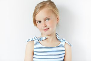 Close up shot of beautiful blonde Caucasian little girl wearing striped dress, looking at the camera with adorable smile, posing against white copy space concrete wall. Happy childhood concept