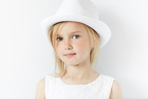 Lifestyle and people concept. Isolated headshot of beautiful Caucasian 5-year old female model with fair hair wearing stylish white clothes, looking and smiling at the camera with happy expression