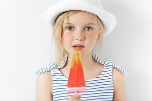 Happy adorable little girl eating ice cream. Beautiful Caucasian child with green eyes and blonde hair, in white hat and striped dress licking popsicle, looking at the camera with serious expression