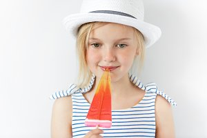 Happy childhood concept. Cute female kid with fruit ice-cream in her hands, looking and smiling down with thoughtdul and dreamy expression on her face. Little girl in stylish clothes holding popsicle