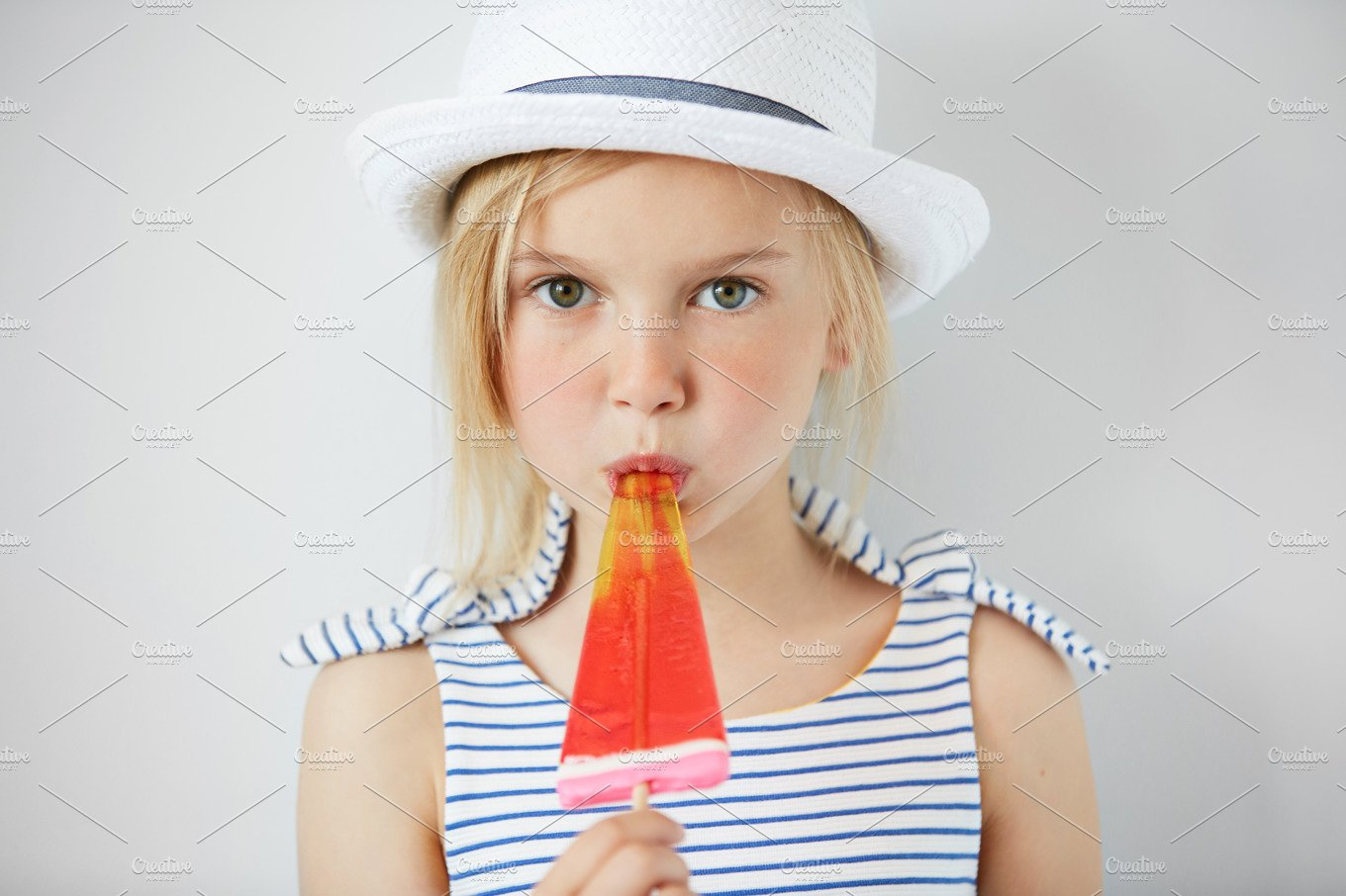 Isolated Shot Of Cute Little Girl With Green Eyes And Blonde Hair Wearing White Hat And Striped