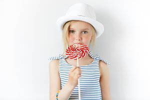 Lifestyle and people concept. Adorable little female child with green eyes and fair hair in white hat and striped dress, posing with candy in her hands, spending weekend with her grandparents