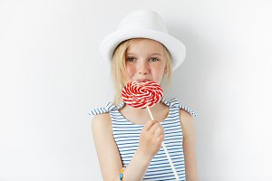 Headshot of beautiful little girl holding and licking huge spiral lollipop, looking at the camera with happy and joyful expression. Adorable blonde child wearing stylish clothes enjoying sweet candy