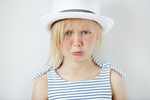 Studio portrait of sad little girl in stylish clothes crying and acting naughty, looking at the camera with angry expression, having trouble with going to bed. Human face expressions and emotions