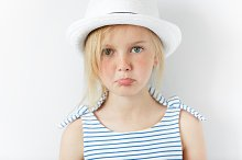 Portrait of beautiful little girl looking at the camera with sad and disappointed expression. Upset Caucasian 5-year old girl wearing stylish clothes against white background. Human face expressions