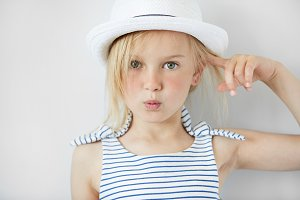Close up shot of  annoyed and angry girl wearing white hat and striped dress, holding index finger at her head with 'are you crazy' gesture. Isolated portrait of little Caucasian 5-year old child