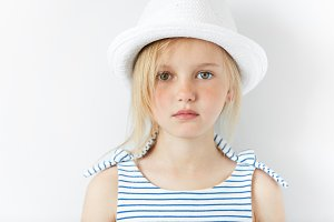 Cute preschool girl with green eyes and blonde hair wearing striped dress and white hat looking at the camera while posing against white studio wall background. Pretty serious little female model
