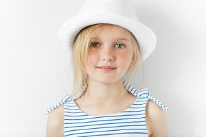 Portrait of cute smiling little girl wearing striped dress and white hat looking with cheerful expression at the camera. Cute stylish blonde preschool kid against white wall. Happy childhood concept